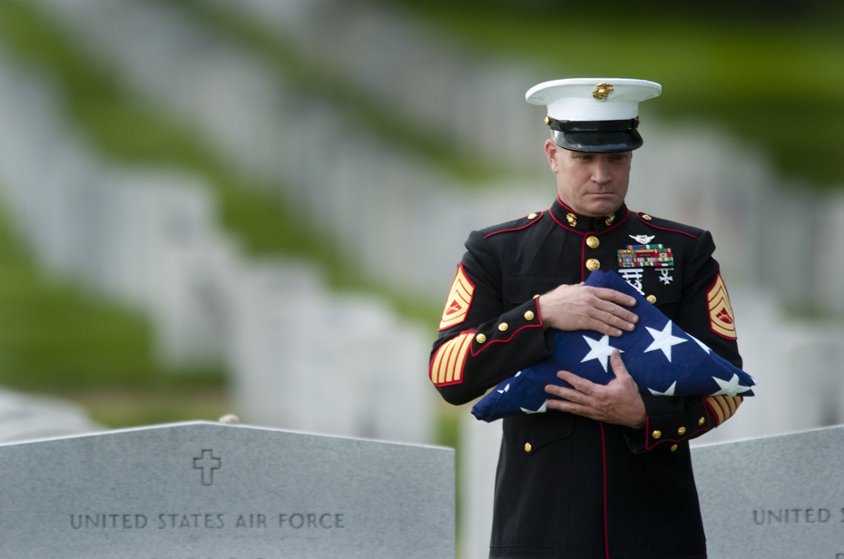 A Marine honor guard holds the flag that covered the casket of a soldier during funeral services at Arlington National Cemetery.