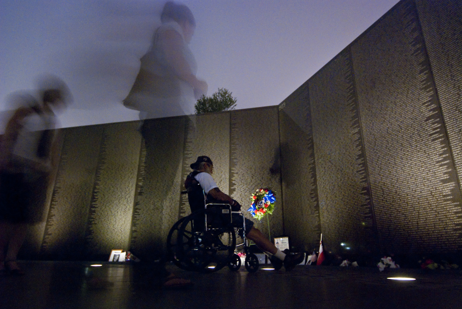"A wheelchair bound veteran visits the Vietnam Veteran's Memorial, also known as ""The Wall."""