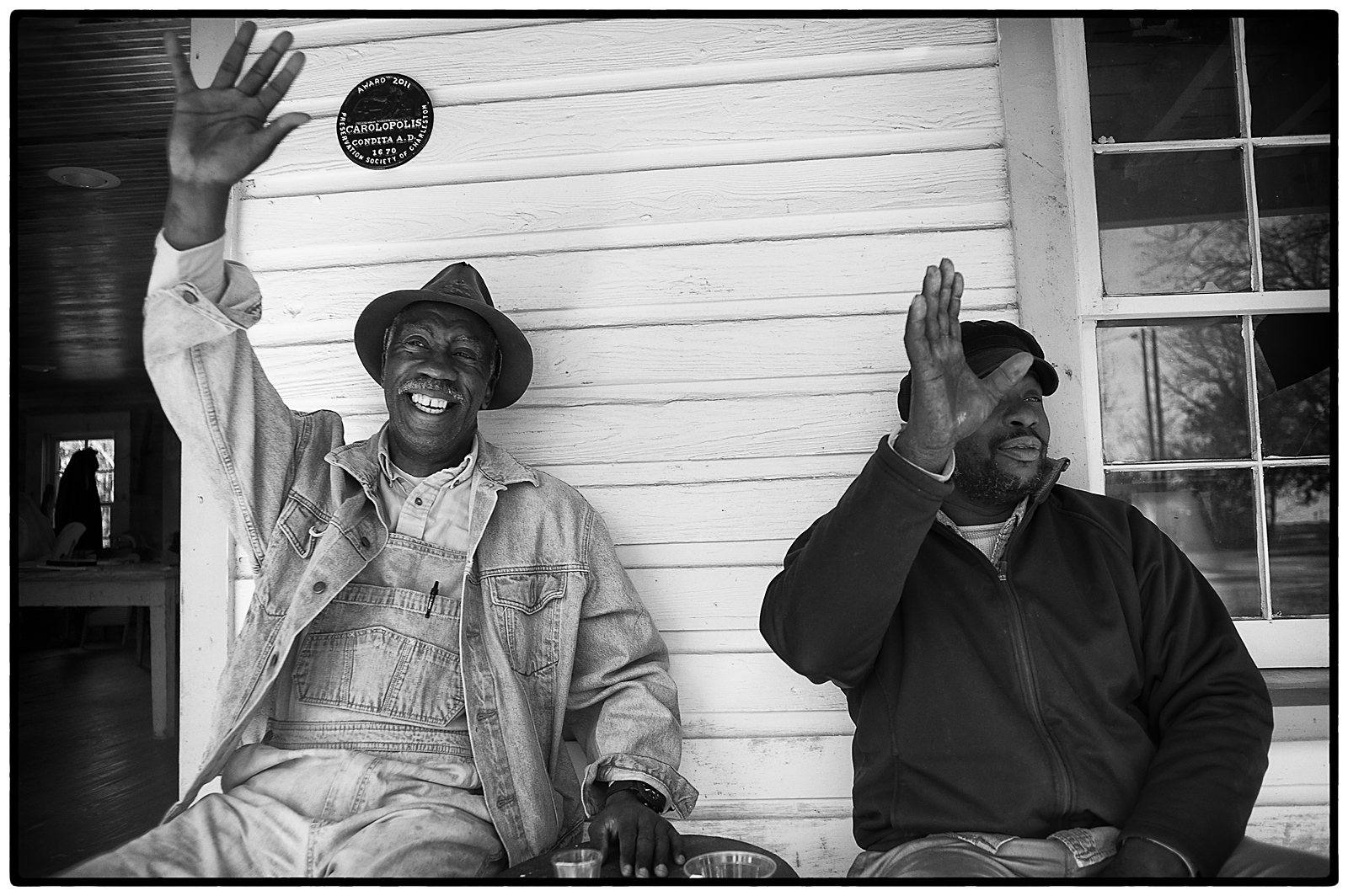 Ernest Parks and James Brown wave to passers-by from the porch of the Seaside Farmers Lodge on Sol Legare.
