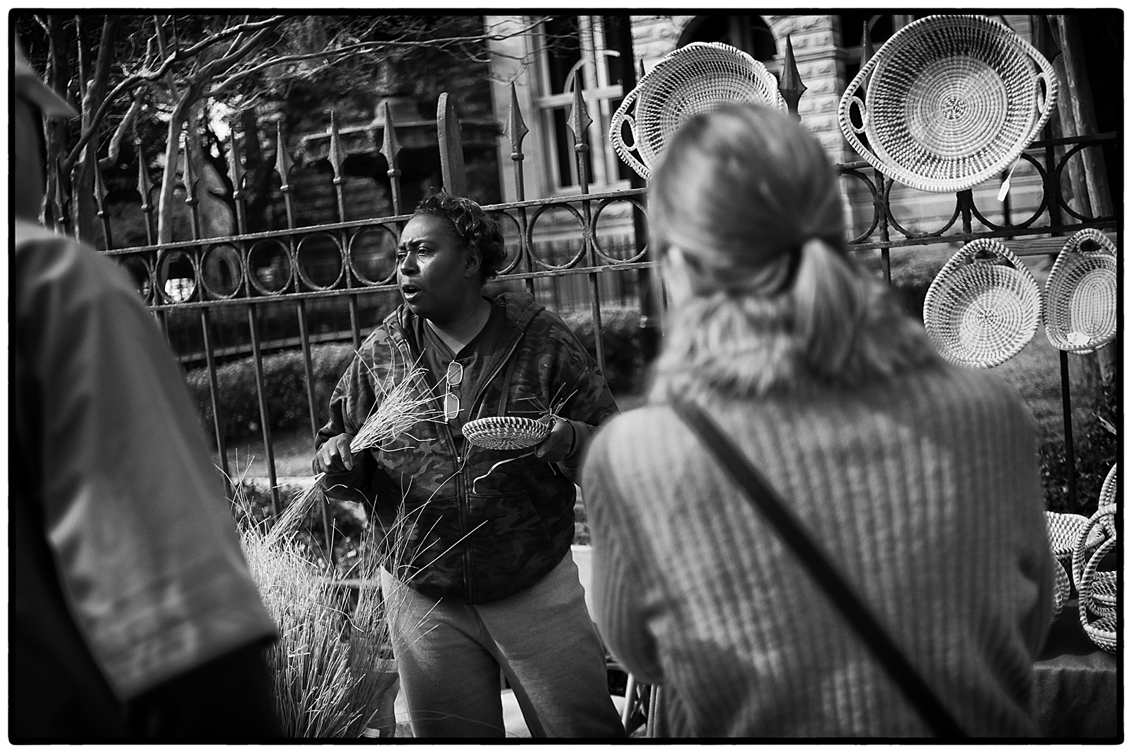 A Gullah sweetgrass basket maker explains the craft to tourists in downtown Charleston, SC.