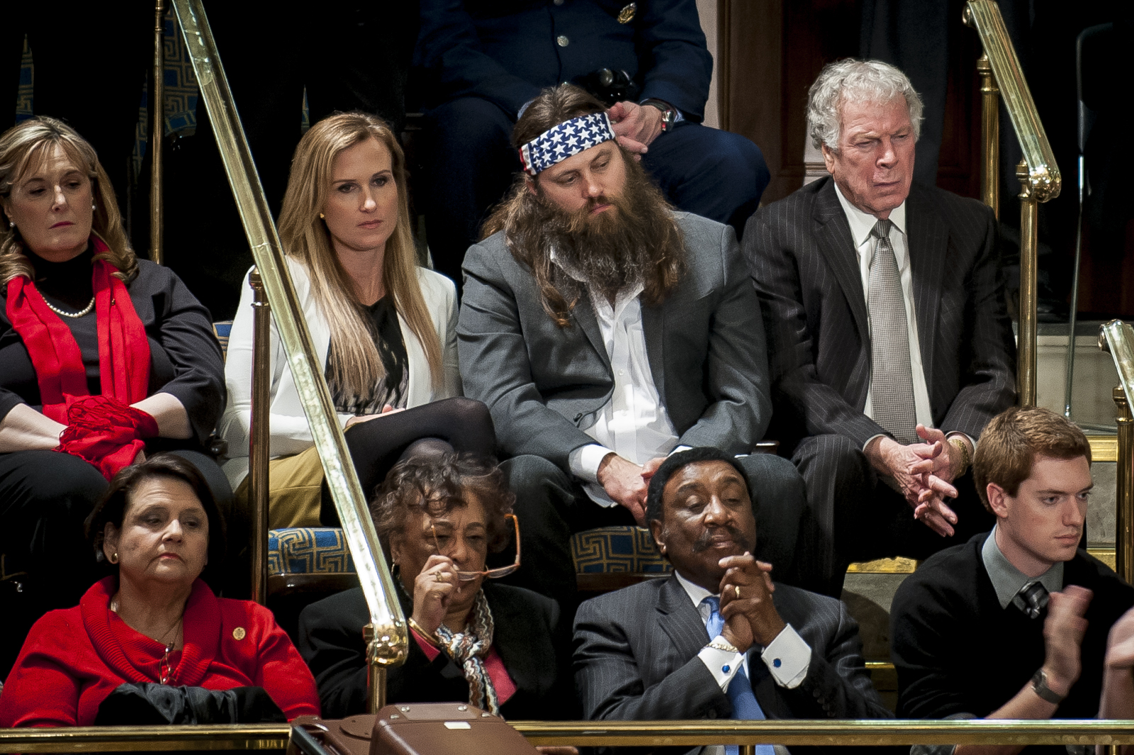 """Duck Dynasty"" cast member Willie Robertson (headband) looks on as U.S. President Barack Obama delivers the State of the Union address to a joint session of Congress at the Capitol in Washington, D.C., U.S., on Tuesday, Jan. 28, 2014. Photographer: Pete Marovich/Bloomberg"