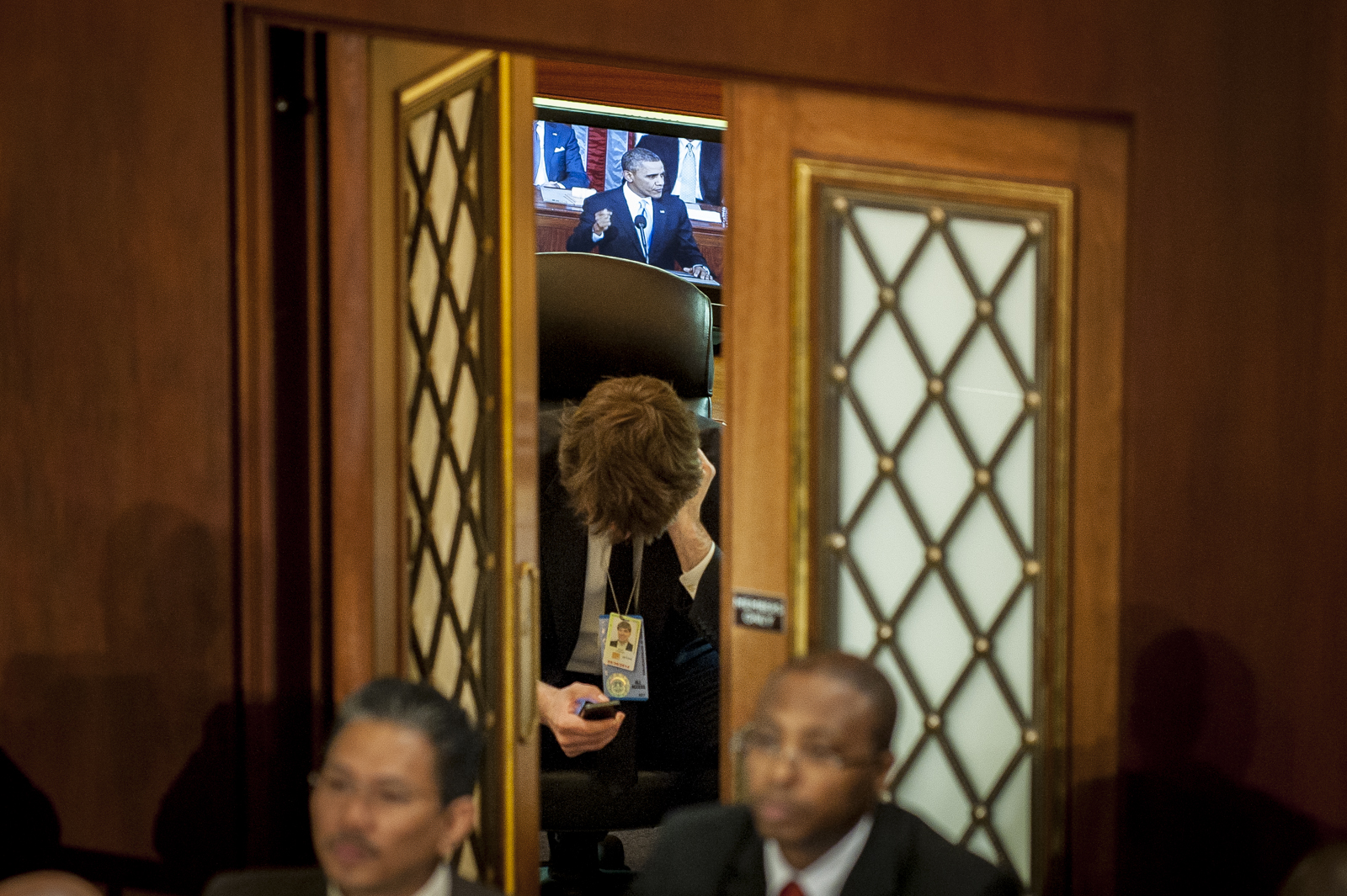 A Congressional Staff member looks on his cellphone in a room adjacent to the House Chamber as U.S. President Barack Obama delivers the State of the Union address to a joint session of Congress at the Capitol in Washington, D.C., U.S., on Tuesday, Jan. 28, 2014. Photographer: Pete Marovich/Bloomberg