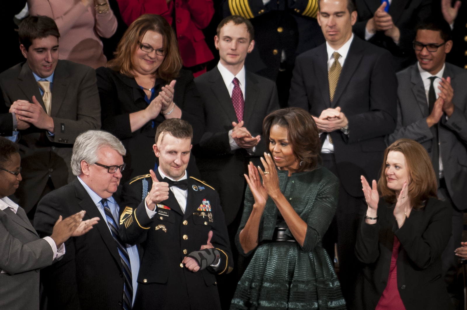 US Army Ranger Sergeant First Class Cory Remsburg gives a thumbs up in acknowledgement of the standing ovation by First Lady Michelle Obama and the entire Congress as U.S. President Barack Obama tells his story in the State of the Union address to a joint session of Congress at the Capitol in Washington, D.C., U.S., on Tuesday, Jan. 28, 2014. Remsburg was wounded by a roadside bomb in Kandahar, Afghanistan on his 10th deployment that left him in a coma for three months, partially paralyzed and brain-damaged. Photographer: Pete Marovich/Bloomberg