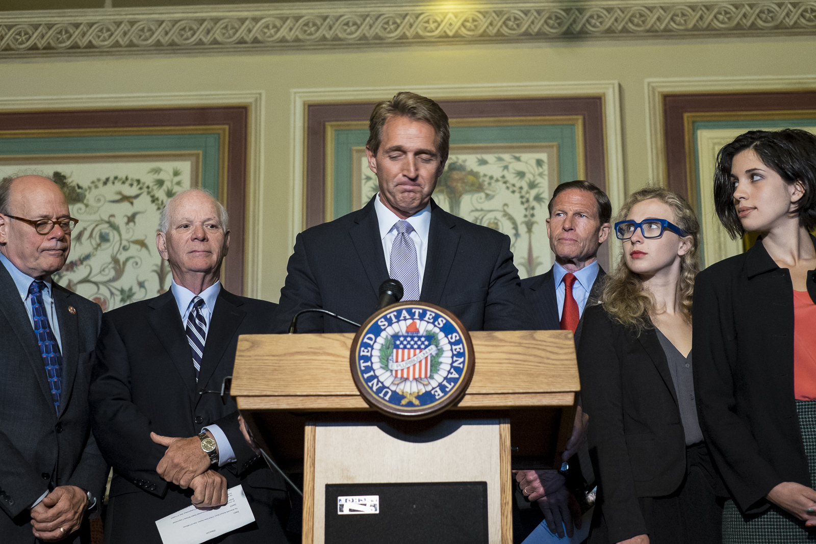Maria Alyokhina (L) and Nadya Tolokonnikova, members of the Russian feminist punk rock protest group, Pussy Riot, look on as Senator Jeff Flake (R-AZ) speaks during a press conference with other members of the Senate Foreign Relations Committee on Capitol Hill in Washington, D.C., to discuss the state of human rights in Russia.