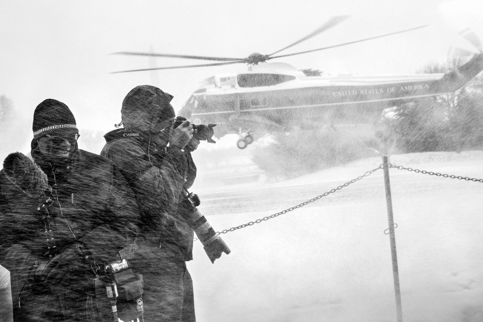 Members of the media turn away from the blowing snow as Marine One comes in for a landing on the snow covered South Lawn of the White House in Washington, District of Columbia, U.S., on Wednesday, Jan. 7, 2015.  President Obama is traveling to the Ford Michigan Assembly Plant in Wayne, Michigan to deliver remarks highlighting the workers in the resurgent American automotive and manufacturing sector now that the auto rescue has been completed and the decision to save the auto industry and the over one million jobs that went with it. Photographer: Pete Marovich/Bloomberg/POOL