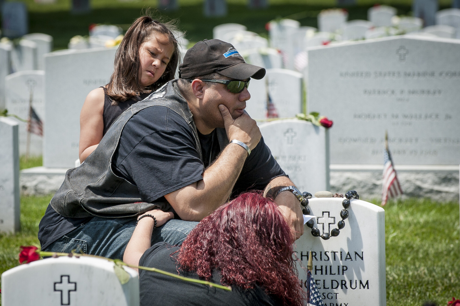 On Memorial Day, Alivin Amezquita is comforted by his wife Erika and daughter Myra as he visits the grave of a friend at Arlington National Cemetery in Arlington, Virginia, USA, on 25 May 2015. (Pete Marovich/ European PressPhoto Agency)
