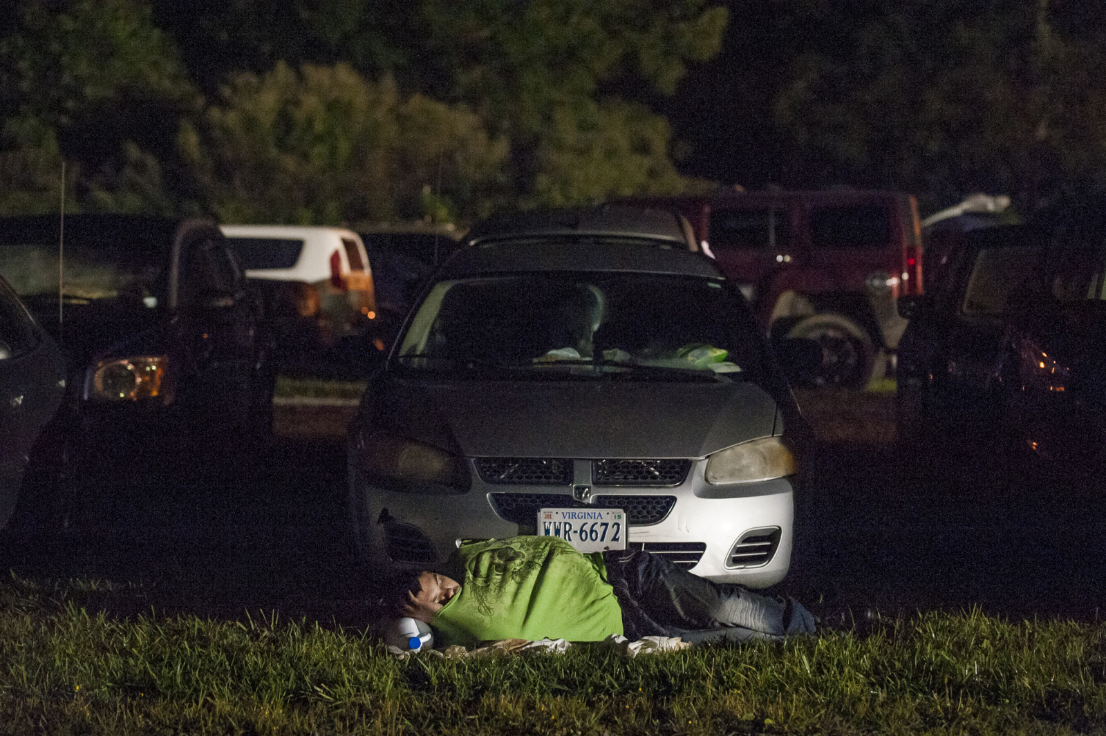 A man sleeps in front of his car in the parking lot at the Wise County Fairgrounds, where people hope to receive free medical care the next day at the 16th annual Remote Area Medical (RAM), clinic in Wise, Virginia, U.S., in the early morning on Friday, July 17, 2015. Photo: Pete Marovich/Bloomberg