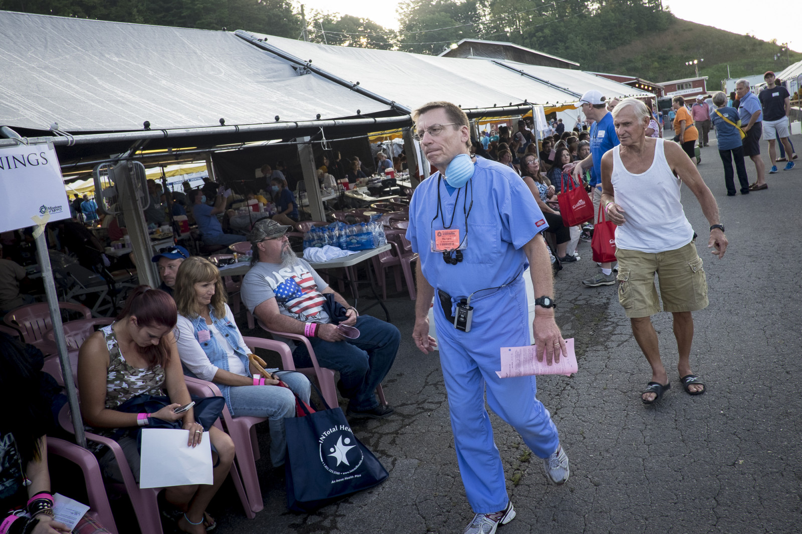 A dentist walks past waiting patients at the 16th annual Remote Area Medical (RAM), clinic in Wise, Virginia, U.S., on Friday, July 17, 2015. Photo: Pete Marovich/Bloomberg