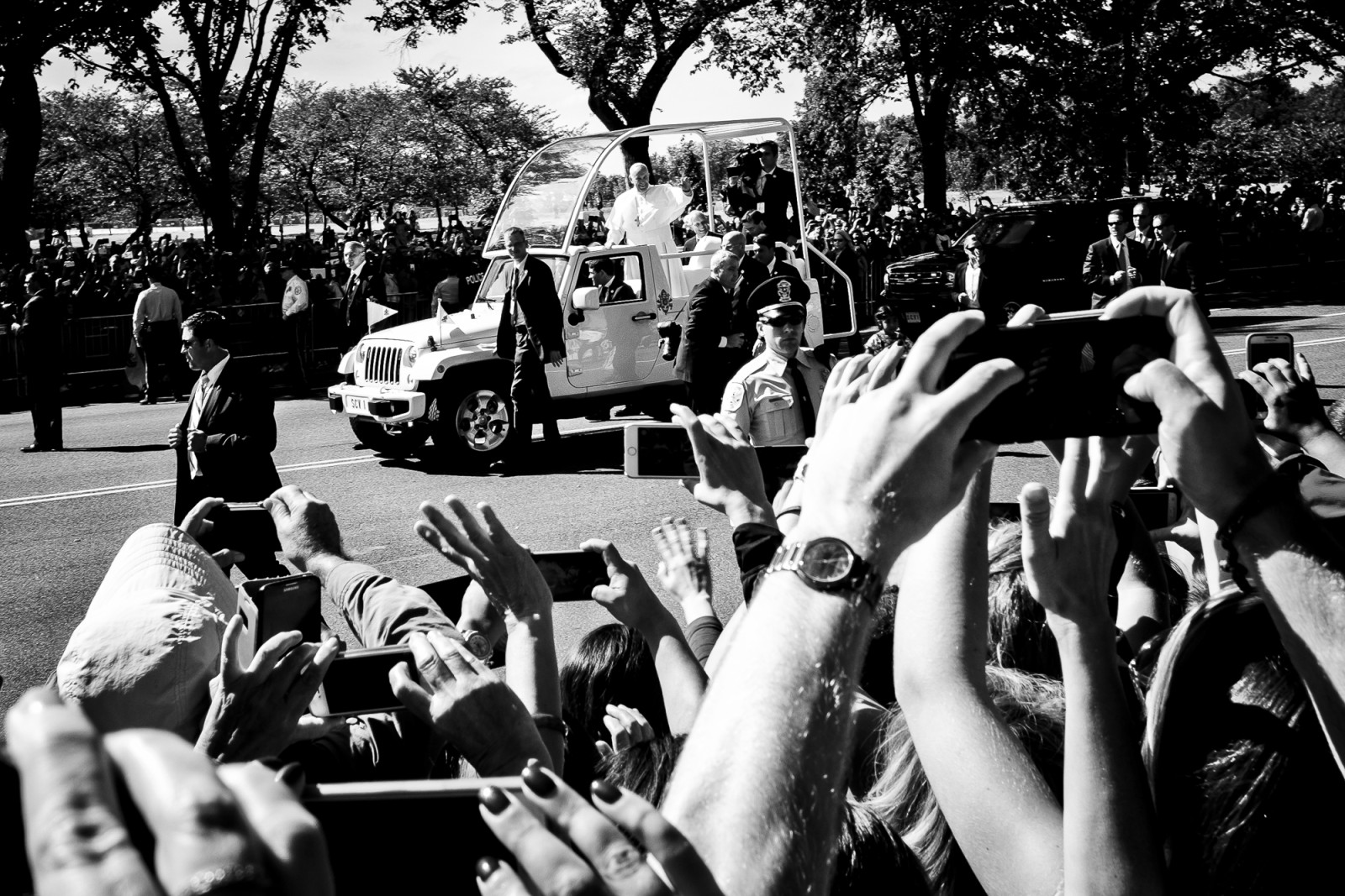 "Spectators cheer for Pope Francis as he passes by in his ""popemobile,"" as he is driven on the streets around the Ellipse, south of the White House in Washington, District of Columbia, U.S., on Wednesday, Sept. 23, 2015.  Credit: Pete Marovich/Bloomberg"