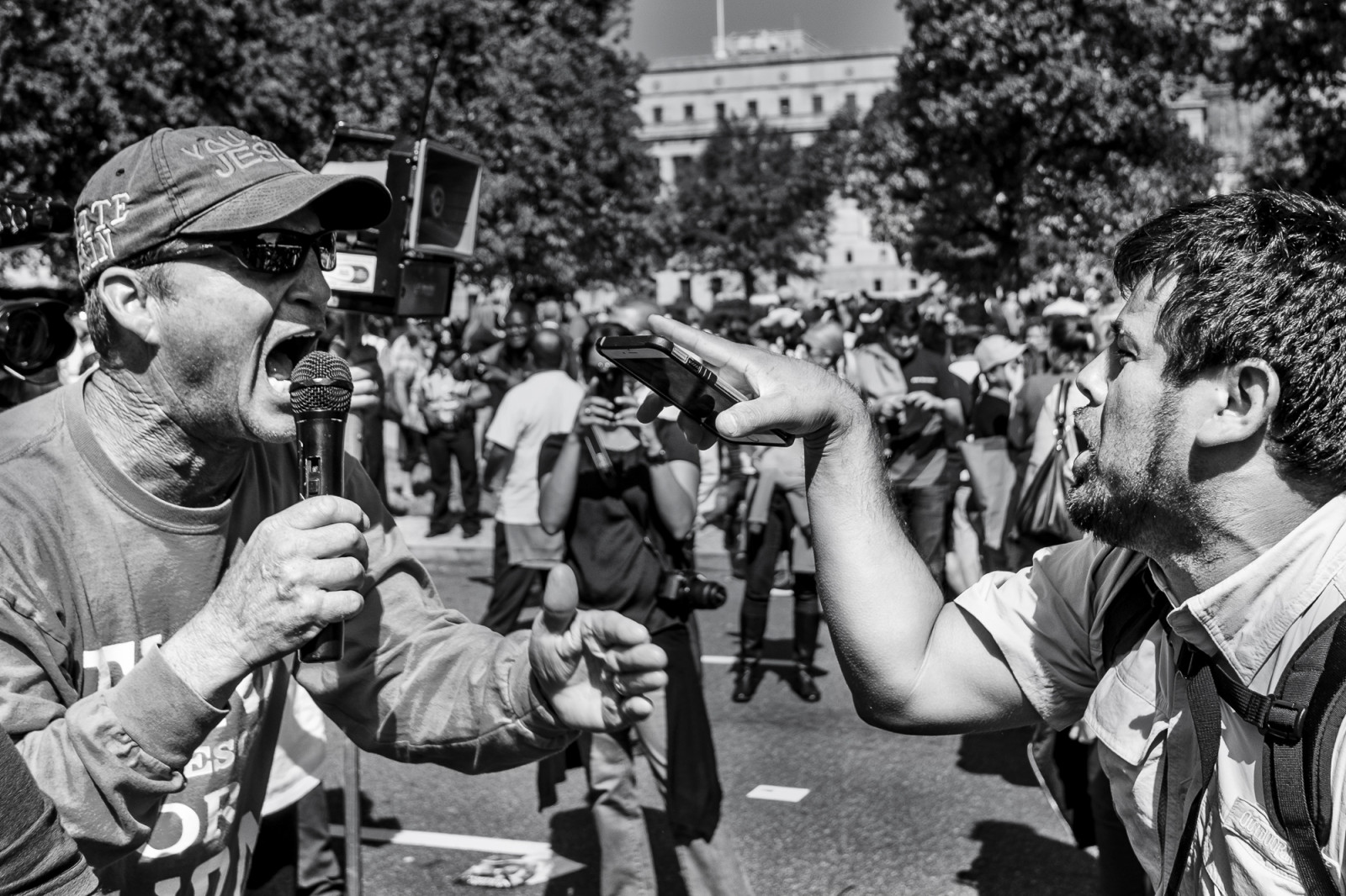 A man from the Los Angeles chapter of Bible Believers (left) and an fan of Pope Francis clash in a war of words following a short parade where Pope Francis was driven on the streets around the Ellipse, south of the White House in Washington, District of Columbia, U.S., on Wednesday, Sept. 23, 2015.  Credit: Pete Marovich/Bloomberg